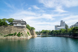 Osaka castle and water next to modern buildings in Japan