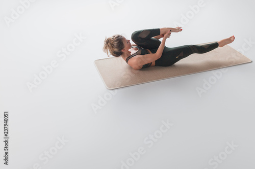 Naklejka Young woman stretching legs on floor
