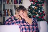 Depressed woman portrait during christmas holiday at home