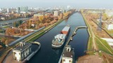 Sluice Gates on the River. Aerial view barge, ship in the river gateway. The movement of ships and barges along the canal through the river gateway in autumn sunny day. - 237943419