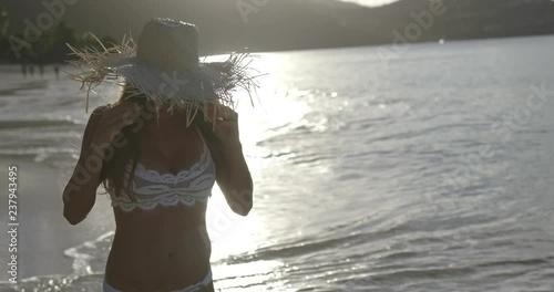 bikini woman with straw hat walking on beach in slow motion