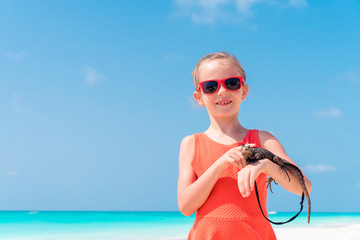 Adorable little girl happily holds a wild tropical lizard on white tropical beach