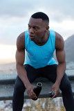 Healthy fatigue dark skinned man takes break after outdoor workout, holds bottle of energy drink, has pensive look aside, models outside alone, refreshes with water, tries to rejuvenate, being strong - 237951024