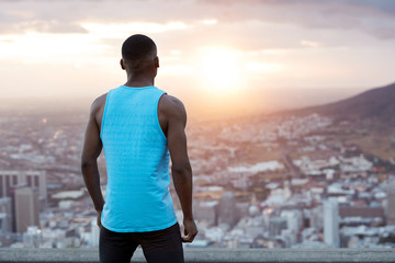 Horizontal back view of athletic man in casual clothes, wears blue vest, takes break after jogging exercise, stands on top in front of magnificent nature view during morning. People, freedom concept