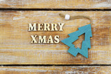 Merry Christmas written with wooden letters and wooden Christmas tree
