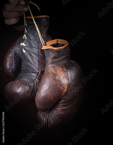 hand holds a pair of brown very old boxing gloves