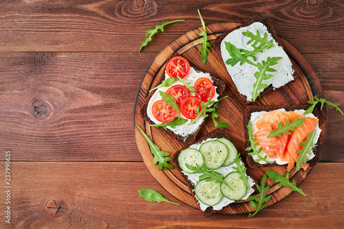 Smorrebrod - traditional Danish sandwiches. Copy space. Black rye bread with salmon, cream cheese, cucumber, tomatoes on dark brown wooden background - 237990635