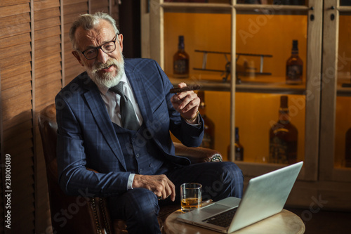 Leinwanddruck Bild Elegantly looking aged grey-haired chief of big company relaxing at restaurant smoking cigar and carrying glass of whiskey while gazing at the screen of laptop and spending time till night sleep.
