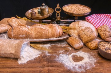 Bread and flour on a rustic wooden table.