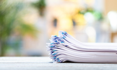 A big stack of documents on a bright interior room background