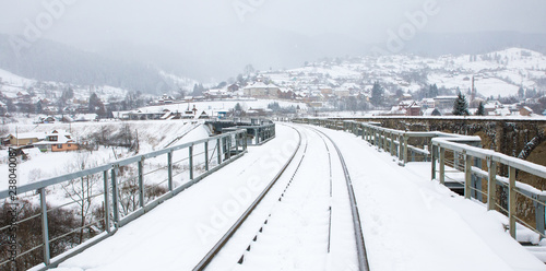 railway in snow on the railway bridge in the mountains - 238040087
