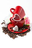 red cups and chocolate candies in the form of heart on white background, vertical top view
