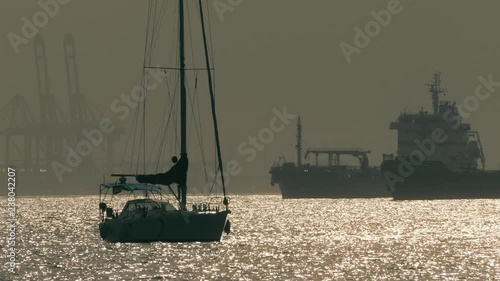 Silhouettes of an unknown anchored sailboat and big cargo ships near Gibraltar