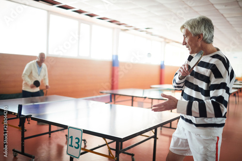 Two active senior men with rackets playing ping pong by large table in the hall