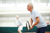 Active mature tennis player with racket and his mate on background concentrating on game