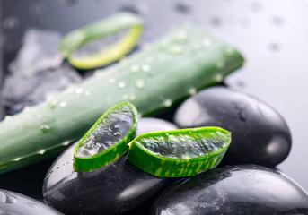 Aloe Vera slices and spa stones closeup on black background. Aloevera plant leaf gel, natural organic renewal cosmetics, alternative medicine. Skincare concept © Subbotina Anna