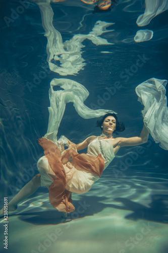 Elegancka smukła dziewczyna pływa pod wodą niczym wolny nurek w białej wieczorowej sukni z piękną tkaniną