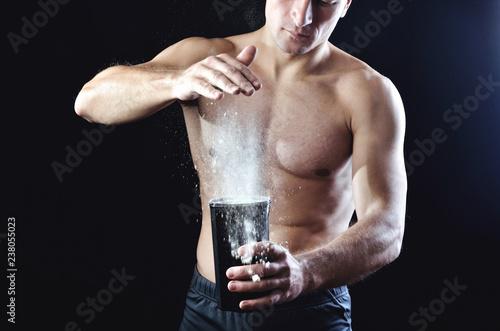 Młody silny sportowiec wlewa suplement białka żywienia w czarny plastikowy shaker na ciemnym tle studio.