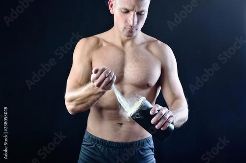 Silny, muskularny sportowiec wylewa suplement diety białkowej do czarnej plastikowej shakera.