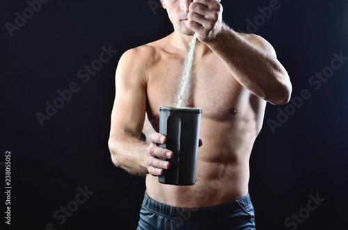Sprawność fizyczna mięśniowy trener nalewa proteinowego odżywianie nadprogram w czarnego plastikowego potrząsacza na ciemnym pracownianym tle.