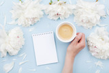 Woman hand with cup of coffee, open notebook and beautiful white peony flowers on pastel table top view. Cozy breakfast in flat lay style. - 238055248
