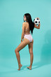 Slim dark-haired girl in sunglasses dressed in pink and white striped swimsuit  holds a soccer ball in her hands on the blue background