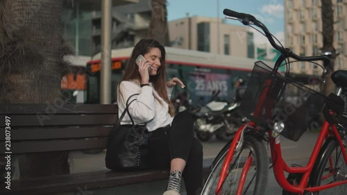 Young woman speaking on mobile phone in summer park on background of morern city. Bicycle woman using smart phone.