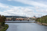 Prague panorama with Stefanik bridge, Vltava river, colorful rooftops, Petrin tower, Prague Castle and St. Vitus Cathedral in the distance, on a cloudy summer day