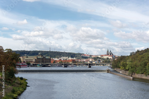 Prague panorama with Stefanik bridge, Vltava river, colorful rooftops, Petrin tower, Prague Castle and St. Vitus Cathedral in the distance, on a cloudy summer day - 238078443