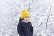 Little boy at a walk in the winter park. Winter games in the yard, fresh air for children in cold weather. Joy outside. Healthy growth. Handsome little boy. Kids fashion.