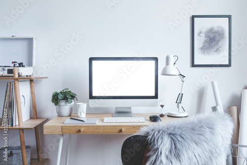 Stylish scandinavian interior of home creative desk with mock up computer screen, poster frame, plants, bookstand and gramophone. Minimalistic space for work, hobby and listen music. Freelancer zone.