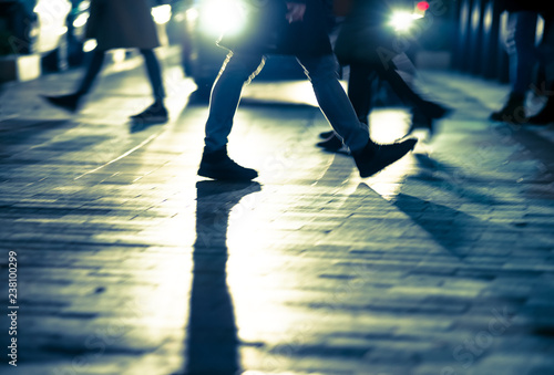 Backlit legs of people crossing the road against car at night