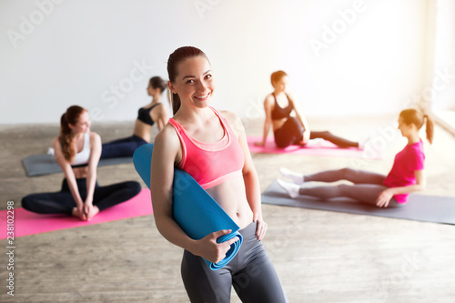Naklejka Young beautiful woman with yoga mat on the background of exercising women.