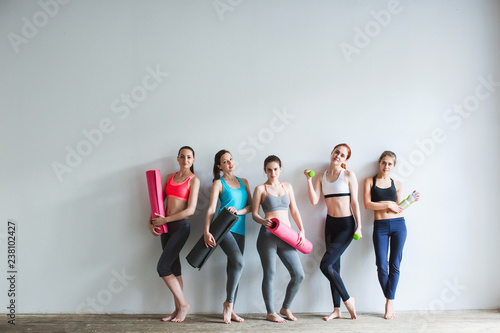 Leinwanddruck Bild Group of female friends in sportswear together standing in a gym after yoga.