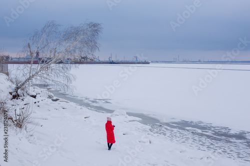 Backside view young woman in long red jacket stands on bank of frozen river with bent birch and looks at pictorial landscape with frozen river and river port under endless blue sky - 238124079