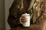 Woman's hand holding cup of coffee with marshmallow