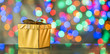 Golden gift box as a symbol of wishes and celebration. Colorful blurred bokeh background.