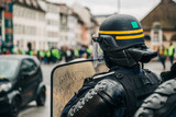 Rear view of police officer wearing helmet and shield securing the zone in frong of the Yellow vests movement gilets jaunes protesters on Quai des Bateliers street . © ifeelstock