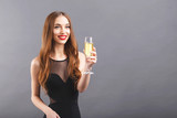Pretty long haired woman with red lips wearing black dress standing on the gray background while says a toast and drinking champagne, New Year, Christmas, holidays, souvenirs, gifts, shopping - 238150470