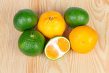 Whole ripe green and orange tangerines and half green tangerine