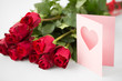love, valentines day and holidays concept - close up of red roses bunch and greeting card with heart