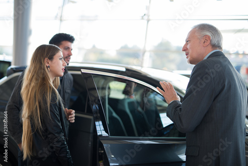 Happy young family talking to the salesman and choosing their new car in a showroom - 238161664