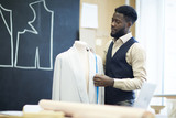 Serious pensive handsome young African-American tailor with beard standing at dummy and taking measures of jacket while working on jacket design - 238162898