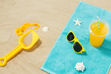 vacation, travel and summer holidays concept - yellow sunglasses, sand toys, seashells and juice drink on beach towel