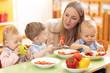 Leinwanddruck Bild - teacher and preschooler kids having break for fruits and vegetables in kindergarten