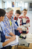 Mature joiner in casual shirt standing at workbench and operating circular saw while demonstrating power tool to young students at practical class - 238166615