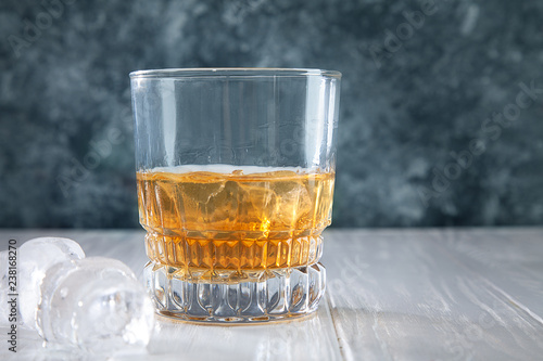 Glass of whiskey or rum with ice on concrete background with copy space for text, logo or brand. Bar concept. Close up view