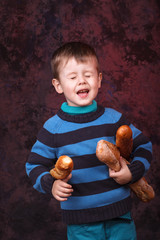 Cute kid holding French bread against dark red background