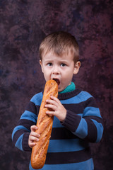 Little boy eating the french baguette. Cute kid holding and biting French bread against dark red background