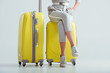 cropped view of woman sitting on suitcases with crossed legs on grey background, travel concept